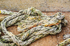 Old faded rope lying on the shore in a fishing port, industry eq Royalty Free Stock Photo