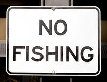 Old Faded White and Black Sign Stating NO FISHING Stock Photo