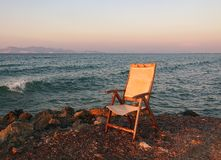 An old fading empty wooden chair in reflected sunset light left next to the sea on a calm summer evening. An old fading empty wooden chair in reflected sunset royalty free stock photos