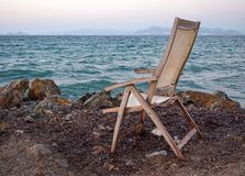 An old fading empty wooden chair on the shore left facing the sea on a calm summer evening. With islands in the background stock images