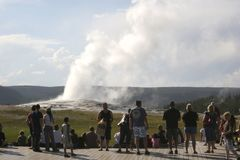 Old Faithful Geyser as seen with the crowd from the benches around the geyser Yellowstone. Old Faithful Geyser as seen with the crowd from the benches around the stock image