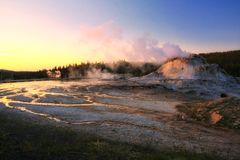 Old Faithful Geyser route at dusk. With twilight light touching sulfur water in Yellowstone National Park in Wyoming, USA stock photos