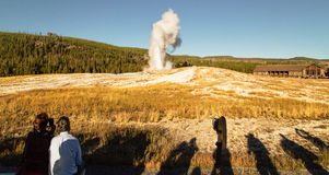 Old Faithful geyser, Yellowstone national park,WY,USA. Tourista watching eruption of Old Faithful geyser at Yellowstone national park Royalty Free Stock Photography