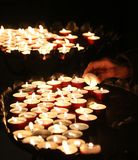 Old faithful hand lights a candle Stock Photos