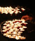 Old faithful hand lights a candle. In church Stock Photos