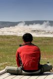 Old faithful meditation. A young man deep in meditation in front of old faithful geyser, yellowstone national park, wyoming stock images
