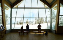 Old Faithful Visitor Center indoor. Unidentifiable visitors inside watching Old Faithful Geyser. Yellowstone National Park Stock Photography