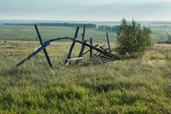Old fallen fence in a summer field stock photography