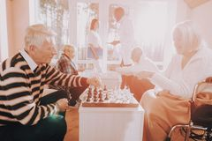 Senior Man and Woman. Play Chess. Nursing Home. Old family with young family. Family together. Aged family smile. doctor with patients. Nurse and patient royalty free stock photos