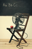 Old fan with apple on chair Royalty Free Stock Photo
