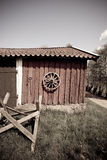 Old farm building. Exterior of old farm building with wagon wheel on timber wall Stock Images