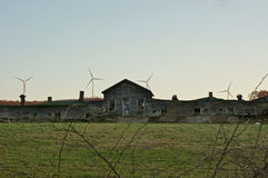 Old Farm Building Backed by Modern Windmills Stock Images