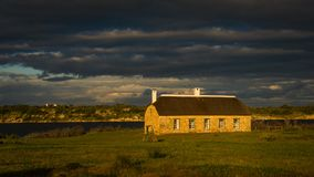 An old farm building is illuminated by the setting sun under a glowering stormy sky. A beam of light from the setting sun shines a spotlight on an old farm Stock Image