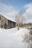 Old farm building on a sunny winter day with snow landscape Stock Photo