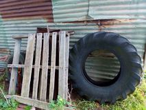 Old farm cottage junk pile. Next to tin shed. Tractor tire and some timber slats stock photography