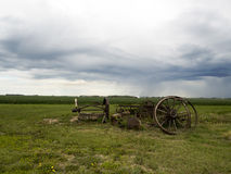 Old Farm equipment scrap metal in the fields:. Landscape of old scrap metal in a farmer`s field Stock Photography