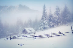 Old farm in the foggy mountains in winter. Retro style Stock Images