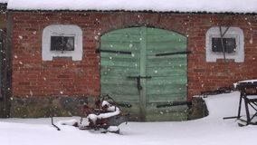 Old farm green door on red wall and winter snowfall stock footage