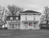 Old farm house in black and white. Old farmhouse in black and white with american flag in front in color Royalty Free Stock Photo