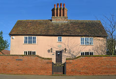 Old farm house with brick wall, gate and period chimney . Stock Images