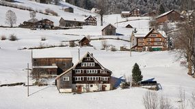 Old farm houses in the Toggenburg valley. Winter scene in the Swiss Alps. Typical architectural style of this region Stock Photos