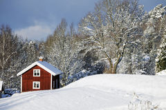 Old farm houses in a winter landscape. Old red farm houses in a snowy winter scenery, dramatic  clouds at the horizon. smaland. sweden Stock Image