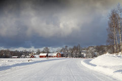 Old farm houses in a winter landscape. Old red farm houses in a snowy winter scenery, dramatic  clouds at the horizon. smaland. sweden Stock Photography