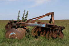 Old farm machinery. Old, rusty farm machinery in a field Stock Photos
