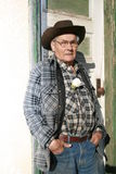 Old Farm Man. Old man standing against an old house door Stock Image