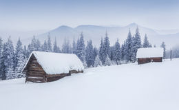 Old farm in the mountains. Foggy winter morning. Stock Photos