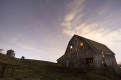 Old farm at Night. The night sky over an old hay barn with light on in the loft and a truck in the distance royalty free stock image