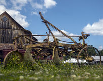 Old farm and rusty harrow in front of a wooden barn Stock Photography