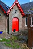 An old farm in Scotland looks like a church, red shutters stand out royalty free stock photography