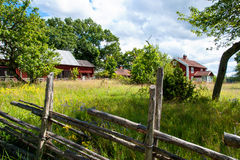 Old farm in Sweden. In the historic province of Småland in summer. Typical red wooden farmhouse, barns and stables. In the foreground a swedish wooden fence Royalty Free Stock Photography