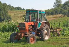 Old farm tractor. Old tractor with plow on a field Royalty Free Stock Images