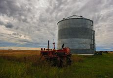 Old Farm Tractor in a field. An old abandoned farm tractor sits in a field beside a granary on the prairies Stock Photo