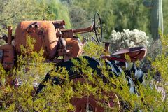 Old farm tractor resting in an overgrown yard stock image