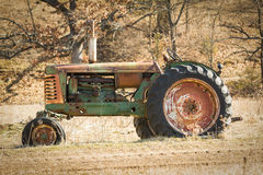 Old farm tractor. Old rusty tractor sits in a winter field Royalty Free Stock Image