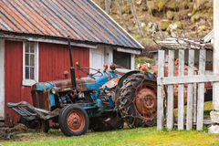 Old farm tractor stands in Norwegian village. Nearby red wooden house royalty free stock photography