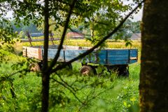 Old farm trailer stands abandoned on a field stock photography