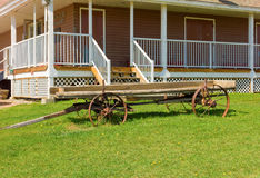 An old farm wagon in front of  a house Royalty Free Stock Photo