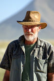 Old Farmer. Bearded man, with his hat on, looking at the camera. There is a mountain faded in the background royalty free stock photos