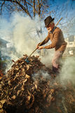 Old farmer burning dead leaves Stock Photos