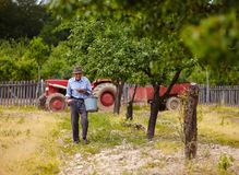 Old farmer fertilizing in an orchard Royalty Free Stock Images