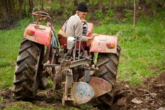 Old farmer plowing. Senior farmer using an old tractor to plow his land Stock Photo