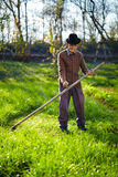 Old farmer with scythe. Senior farmer mowing the lawn with a scythe, traditionally Royalty Free Stock Photo