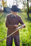 Old farmer sharpening scythe Royalty Free Stock Photos