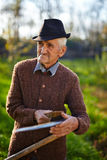 Old farmer sharpening scythe Stock Photography