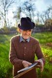 Old farmer sharpening scythe Stock Photo