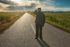 Old farmer standing in middle of the road Royalty Free Stock Image